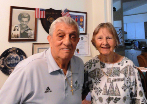John and Joan Tedesco stand before a wall filled with World War II memorabilia including John's service photograph.